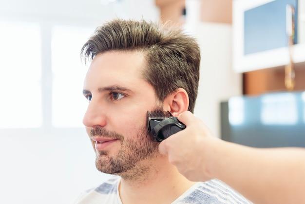 自宅でその場しのぎの美容院で若い男の髪を切る女性