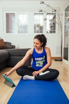 オンラインクラスを見て、自宅でヨガの練習の女性