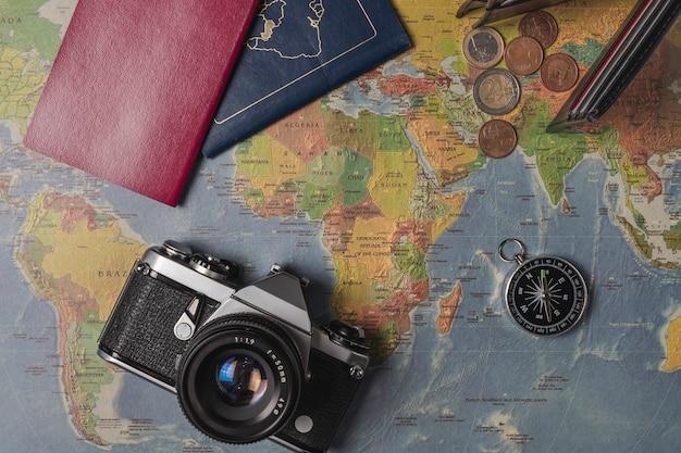 世界地図に設定された旅行。財布、ユーロ、カメラ、パスポート、コンパス...
