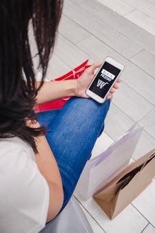 Молодая девушка сидит с сумками на полу и смотрит на свой мобильный приложение черная пятница