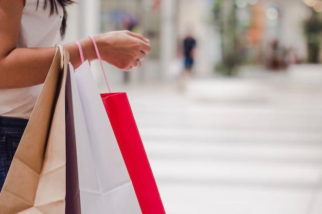 Женщина, держащая некоторые сумки стоя в торговом центре. горизонтальное изображение.