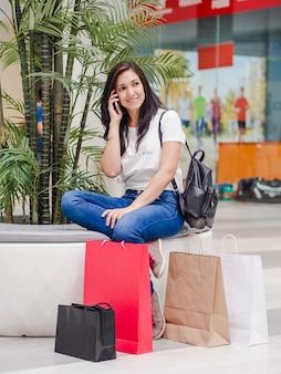 Молодая девушка, сидя в торговом центре, разговаривает по телефону с сумками на полу.