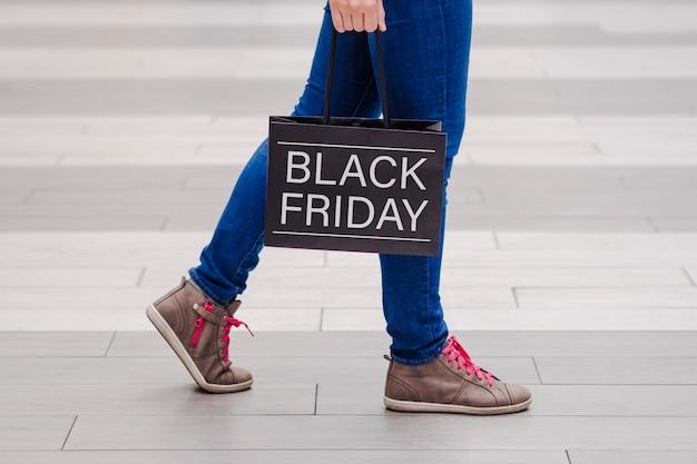 Молодая девушка, ходить вокруг торгового центра с сумкой. черная пятница.