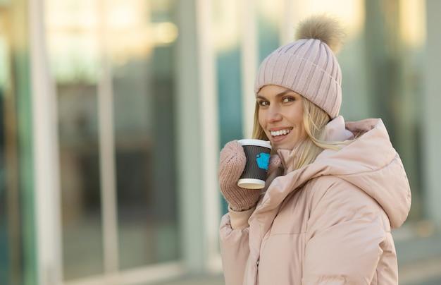 Милая молодая кавказская подростковая женщина в бежевой шляпе с помпоном и розовыми варежками держит дымящуюся чашку горячего чая или кофе, на открытом воздухе в солнечный зимний день.