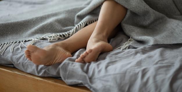 灰色の毛布の横顔の下で女性の足。ベッドの上の美しい若い女性の足。