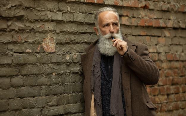 長いひげ喫煙屋外でエレガントな紳士。