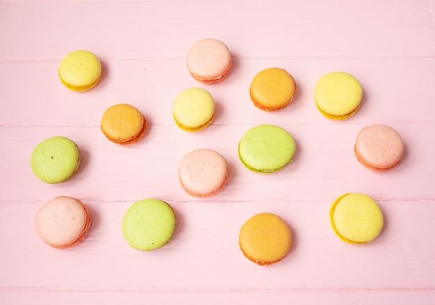 ピンクのテーブルに色とりどりのマカロン