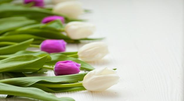 木製の背景に春のチューリップの花。チューリップ、ガーデニングのコンセプトです。