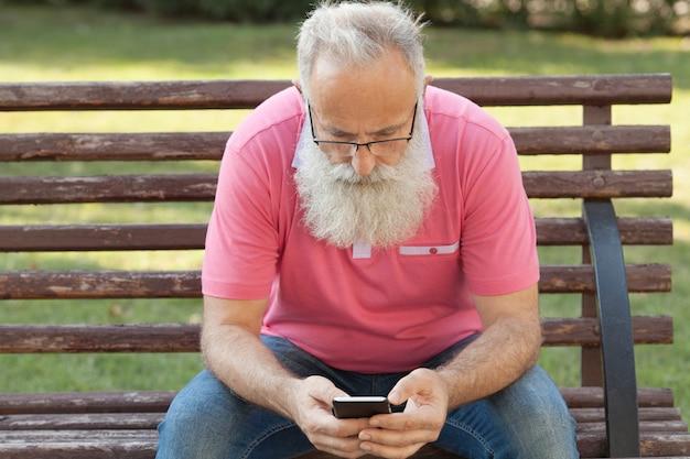 電話を使用してベンチにひげを生やした男