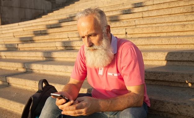 電話で男のテキストメッセージ。階段の上に座って通りで携帯電話を持つ現代のシニア男性。