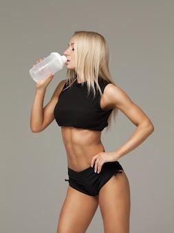 灰色の背景に対して隔離されるスポーティな筋肉女飲料水