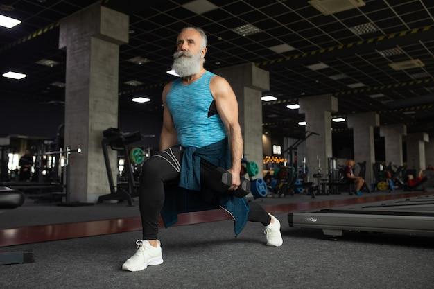 重みでワークアウトのジムでスポーツ衣料の年配の男性。