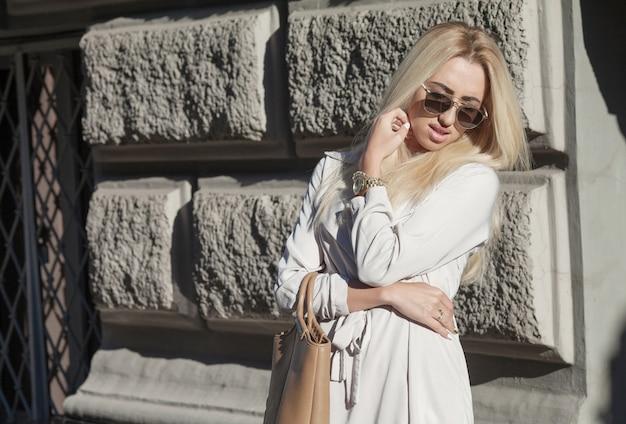 スタイリッシュなサングラスと夕暮れ時のファッショナブルなバッグの美しい少女。