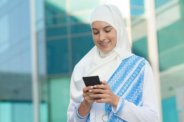 屋外の携帯電話で美しいイスラム教徒の女性のテキストメッセージ。
