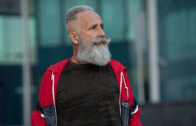 街を歩いてアクティブなシニア男性。外に立っている間ひげを持つシニア男の肖像画。