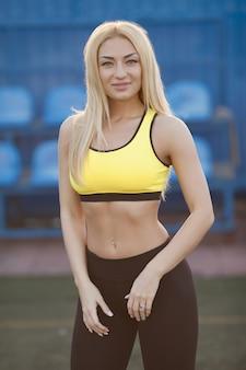 Фитнес и образ жизни концепция - красивая улыбающаяся женщина, занятия спортом на открытом воздухе