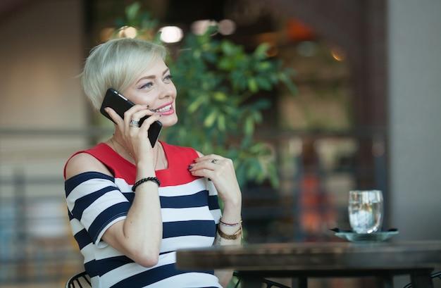 Красивая и счастливая женщина средних лет разговаривает по мобильному телефону