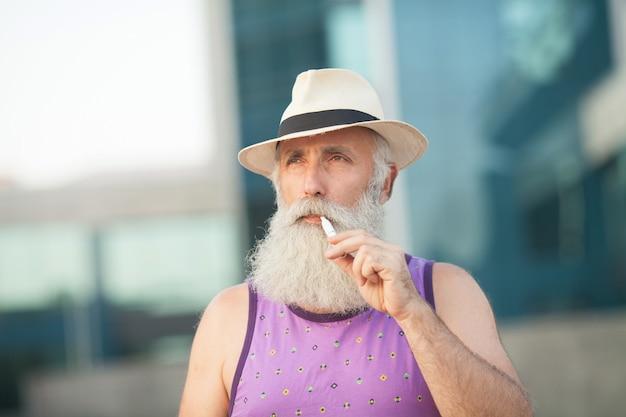 Съемка крупным планом стильного зрелого бородатого человека в яркой фиолетовой футболке и шляпе. стоять и смотреть на небо и курить.