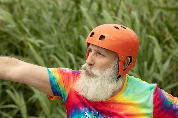 ひげを生やした年配の男性が深刻な一見ラフティングの準備をしています。