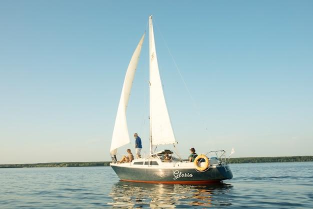 セーリングと湖で帆船のホイールに座って幸せな先輩カップル。