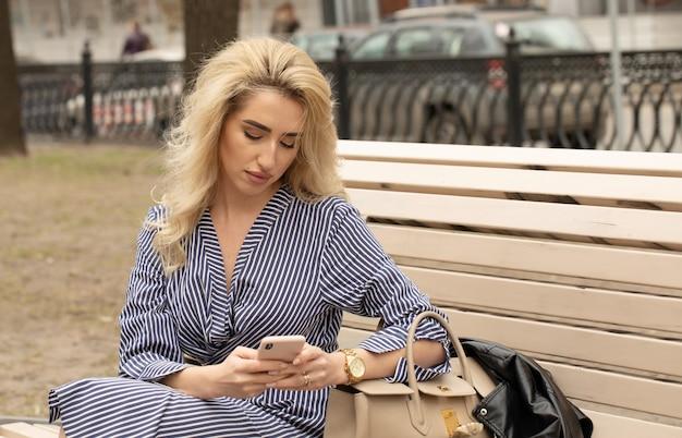 コーヒーブレークを取り、スマートフォンを使用して実業家