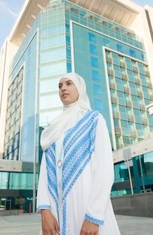 屋外を考えながらスカーフを身に着けている若いイスラム教徒の女性の肖像画