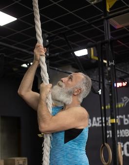 ひげを生やした年配の男性がジムでロープを使って運動します。身体活動と健康的なライフスタイル。