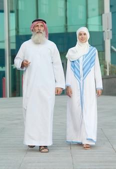 Арабская пара улыбается и стоит на фоне улицы