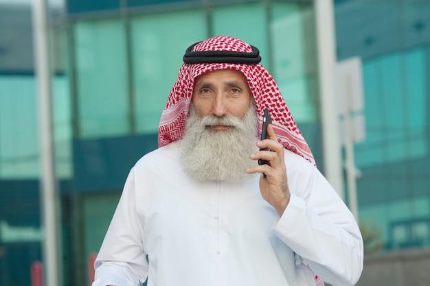 Арабский бизнесмен работает со своим телефоном на улице в фоновом режиме