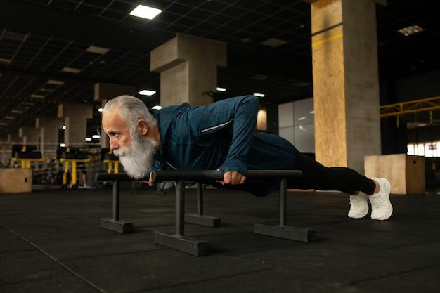 Серьезный бородатый старший мужчина наслаждается спортивным стилем жизни