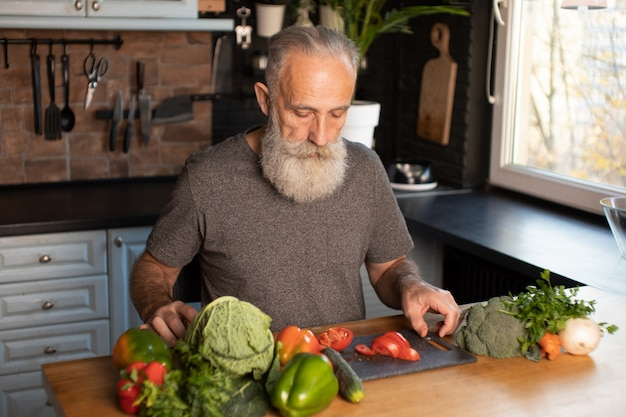 Бородатый старший мужчина нарезка овощей на деревянной доскебородатый старший мужчина нарезка овощей на деревянной доске