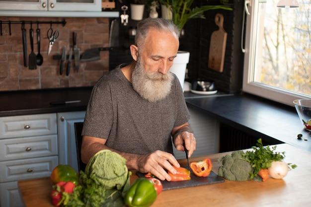 ひげを生やした年配の男性人が木の板に野菜をカット