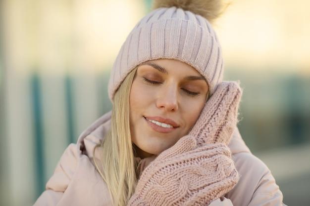 ピンクのニット帽子とミトンの美しい若いモデルの肖像画。ニットの手袋を身に着けている美しい自然の若い笑顔金髪女性
