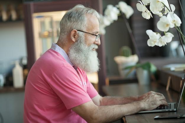 コーヒーショップでコーヒーを飲んで、彼のラップトップに取り組んでいるシニア成熟したビジネス人