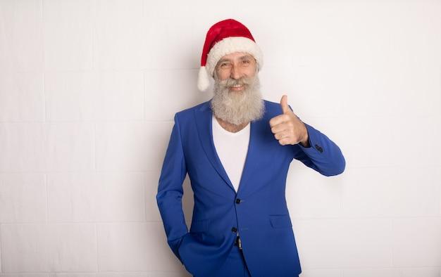 白で分離された彼の手を指しているサンタクロース。紺のスーツのひげを生やした男。サンタ帽子をかぶっているビジネスマン。クリスマス。新年。