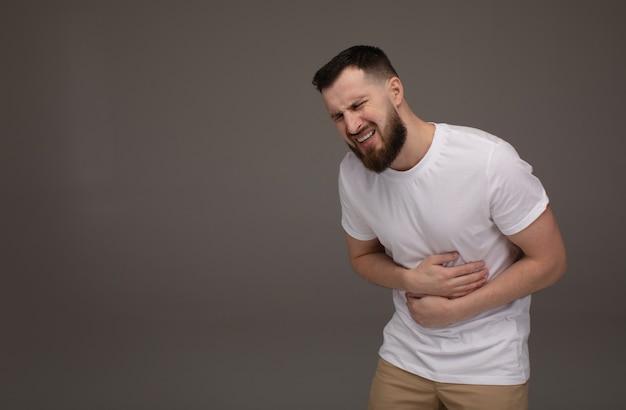 人、医療、問題のコンセプト。灰色の背景上の胃の痛みに苦しんでいる不幸なひげを生やした男