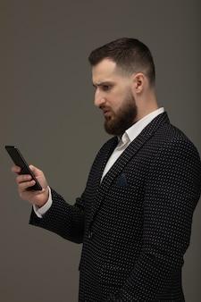 Сообщение молодого человека отправляя смс на умном телефоне изолированном на серой предпосылке.