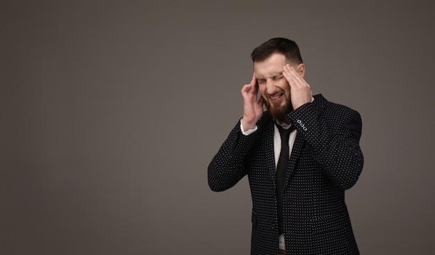 若いハンサムなひげを生やしたビジネスマンストレスのため頭痛に手で灰色の背景の上にスーツを着ています。片頭痛に苦しんでいます。