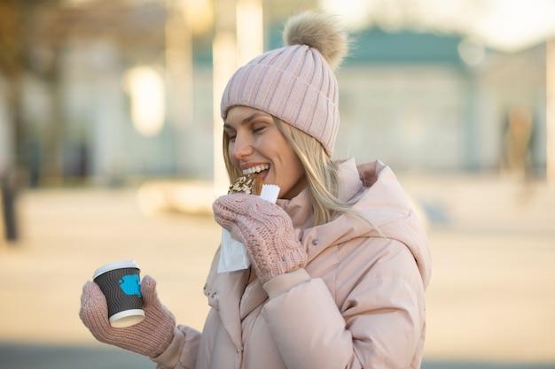 Красивая улыбающаяся молодая женщина в теплой одежде с чашкой горячего чая или кофе. женщина ест печенье на открытом воздухе.