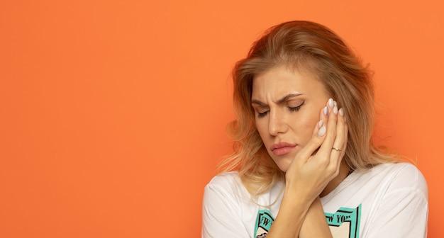 歯の痛みと歯科。ひどい強い歯の痛みに苦しんでいる美しい若い女性。手で頬を触る。オレンジ色の背景に痛みを伴う歯痛を感じる女性。