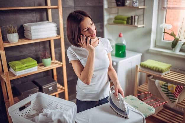 服をアイロンしながら電話で話している女性