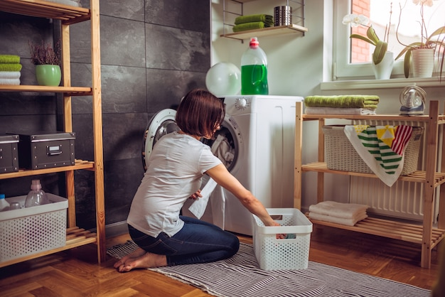 Женщина кладет одежду в стиральную машину