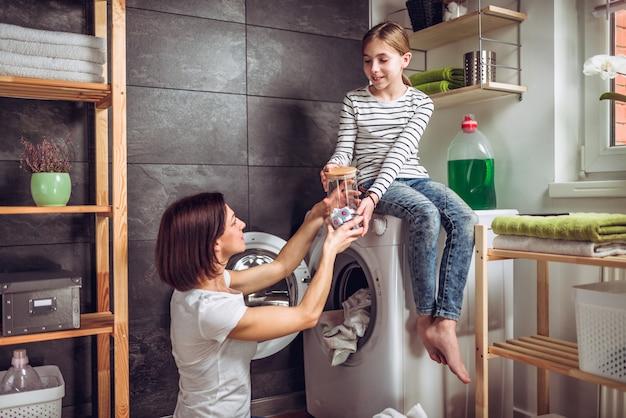 娘が母の服を洗うのを手伝います