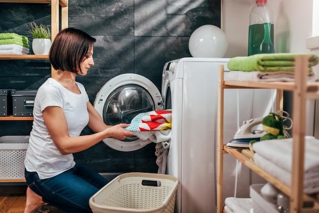 Женщина берет одежду из стиральной машины
