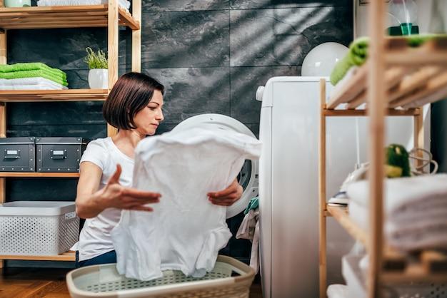 洗濯乾燥機から服を取る女性