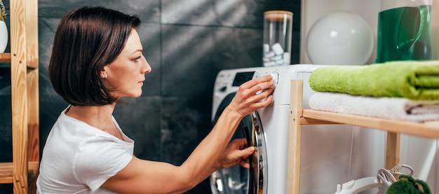 Женщина выбирает программу на стиральной машине