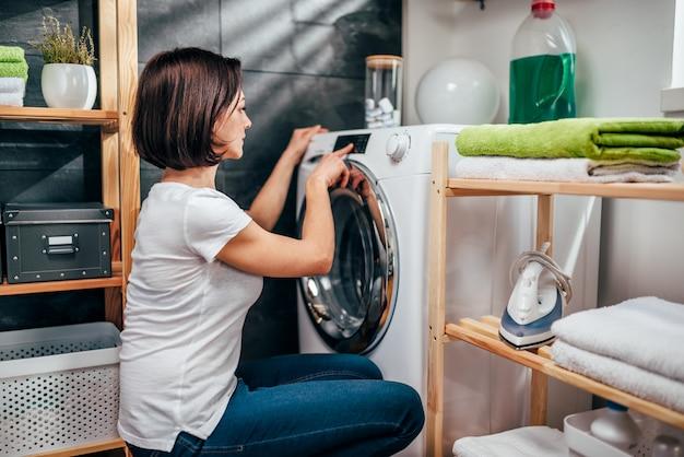 洗濯機でプログラムを選択する女性
