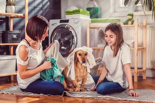 母、娘、犬のランドリールームで楽しんで