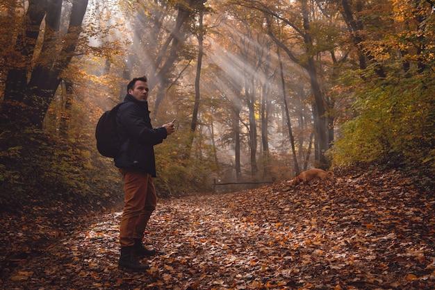 Человек с помощью телефона в лесу