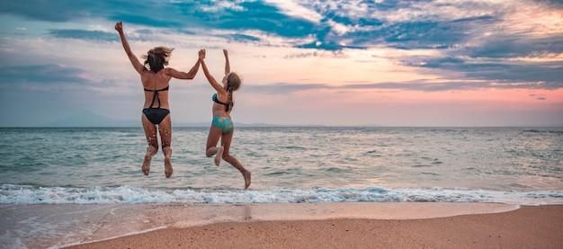 ビーチで楽しい時間を過ごしてのんきな母と娘